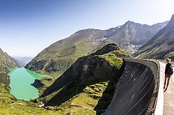 THEMENBILD - Hochgebirgsstauseen Kaprun. Sie dienen der Verbund AG zur Wasserspeicherung für die Stromerzeugung des Kraftwerks Kaprun und sind ein beliebtes Ausflugsziel fuer zahlreiche Touristen, die Mittels Busse und einem Schraegaufzug auf ueber 2000 Meter befoerdert werden. Der Spatenstich erfolgte 1939, ausgefuehrt von Hermann Goering. Seit 1999 gehoert es zur Verbund Hydro Power AG, dem Tochterunternehmen für Wasserkrafterzeugung der Verbund AG, im Bild eine weibliche Touristin auf der Staumauer des Mooserboden Speichers blickt hinunter auf den Speicher Wasserfallboden und das Kapruner Tal. Bild aufgenommen am 27.07.2012. EXPA Pictures © 2012, PhotoCredit: EXPA/ Juergen Feichter