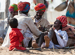 """© Licensed to London News Pictures. 21/11/2012. Pushkar, India. Indian camel & livestock traders rest in the sun at the Pushkar Camel Fair in Rajasthan, India. The Pushkar Fair, or Pushkar ka Mela, is the annual five-day camel and livestock fair, held in the town of Pushkar in the state of Rajasthan, India. It is one of the world's largest camel fairs, and apart from buying and selling of livestock it has become an important tourist attraction and its highlights have become competitions such as the """"matka phod"""", """"longest moustache"""", and """"bridal competition"""".  Photo credit : Richard Isaac/LNP"""