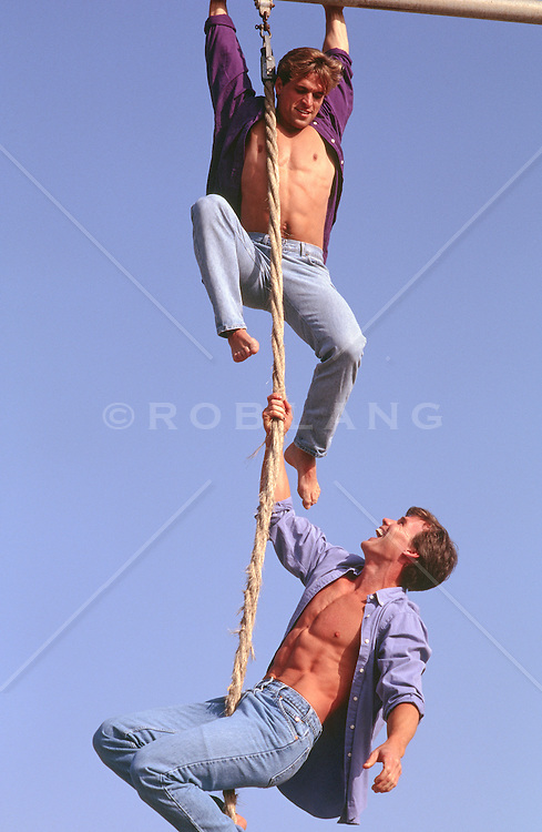 two men playing around together on a climbing rope outdoors