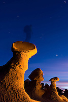 A hiker stands atop a glowing hoodoo at dusk in Goblin Valley State Park, Utah.