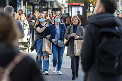 Licensed to London News Pictures. 22/10/2021. London, UK. Early Christmas shoppers wear masks on Oxford Street, London today as Sage urges the government to be ready for a rapid deployment of stricter Covid measures if cases rise too quickly this winter. This week, Health Secretary Sajid Javid predicted new infections could rise to 100,000 a day this winter and urged eligible members of the public to get their booster jabs as soon as possible. Photo credit: Alex Lentati/LNP