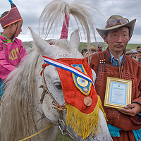 A proud father displays a plaque won by his costumed son, who rode bareback and barefoot in a 20km race at a traditional naadam festival near Muren, Mongolia. Victories in these competitions are a source of great family pride. (The medal on the horse is from an earlier race).