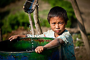 Naga villagers collect rainwater for drinking in steel drums transported from the Chindwin River.