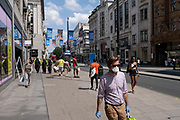 As some non-essential shops re-open, shoppers wearing face masks return to Oxford Street while social distancing measures are put in place by the various retail shops which are open on 26th June 2020 in London, England, United Kingdom. As the July deadline approaces and government will relax its lockdown rules further, the West End remains quiet, apart from this popular shopping district, which itself has far fewer people on its pavements than normal.