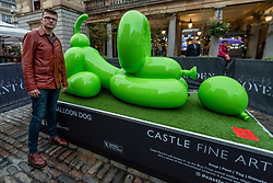 © Licensed to London News Pictures. 07/10/2021. LONDON, UK. Artist Whatshisname (real name Sebastian Burdon) poses with his work Happy Balloon Dog installed in Covent Garden. In total, four colourful balloon dogs are on display until the end of October.  The public are encouraged to take photos and post them to social media with a hashtag #castleforbluecross and Castle Fine Art will donate £1 to the Blue Cross animal welfare charity for each post..  Photo credit: Stephen Chung/LNP