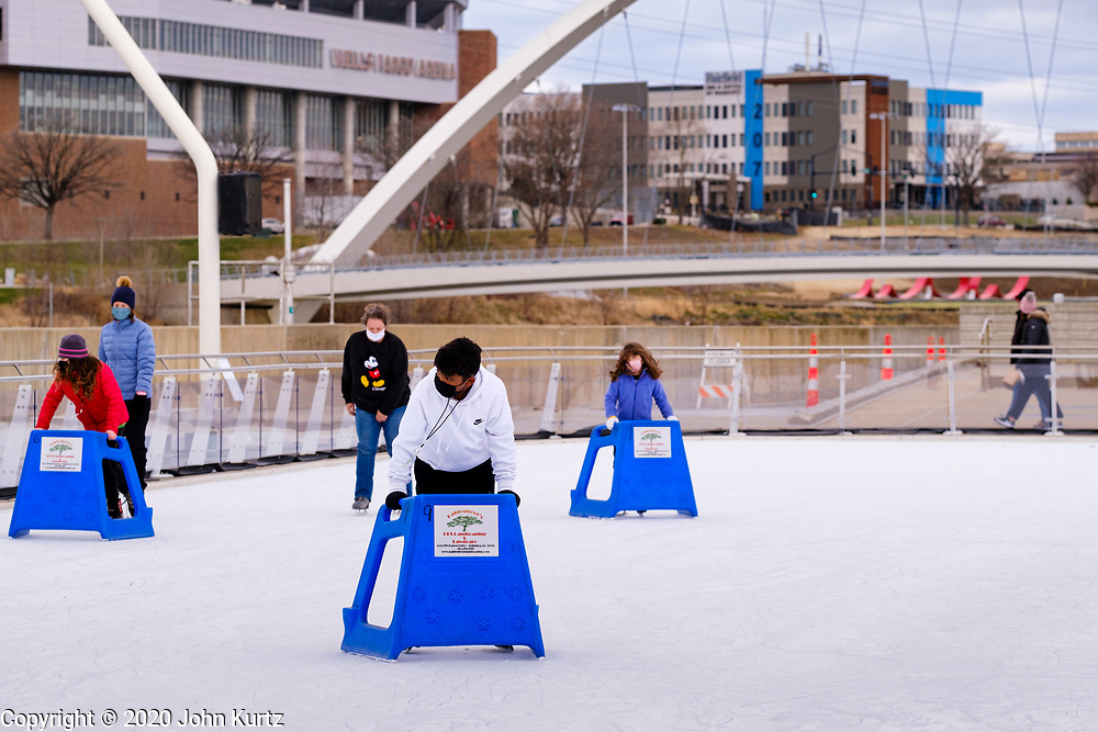 """29 NOVEMBER 2020 - DES MOINES, IOWA: People ice skate at Brenton Skating Plaza in the East Village of Des Moines. Brenton Skating Plaza recently reopened for the season in accordance with Iowa's Coronvirus guidelines. The capacity of the skating rink is one half of normal, skaters have to wear face masks, and they are encouraged to """"social distance"""" while they are on the ice.        PHOTO BY JACK KURTZ"""