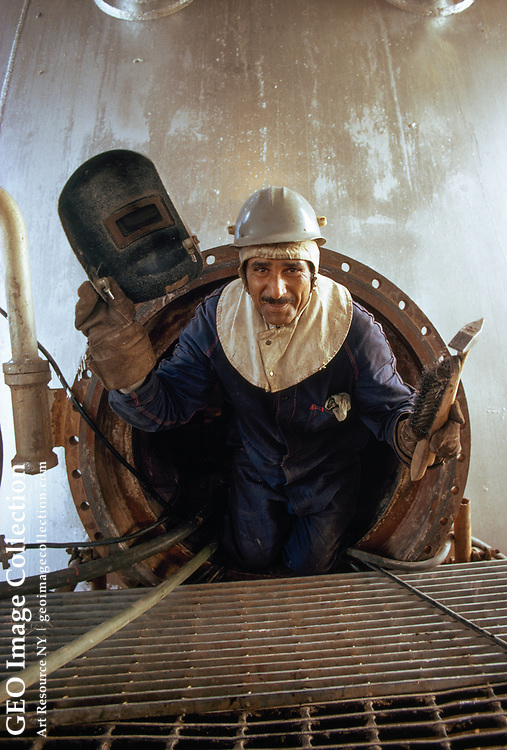 Iranian welder climbs from catalytic cracker hatch at oil refinery.