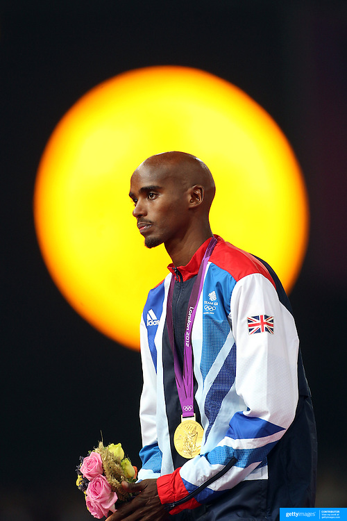 A humble Mo Farah, Great Britain, on the podium with a giant gold medal symbol displayed on the stadium screen behind him as he receives his Gold Medal for his win in the Men's 5000m Final at the Olympic Stadium, Olympic Park, during the London 2012 Olympic games. London, UK. 11th August 2012. Photo Tim Clayton