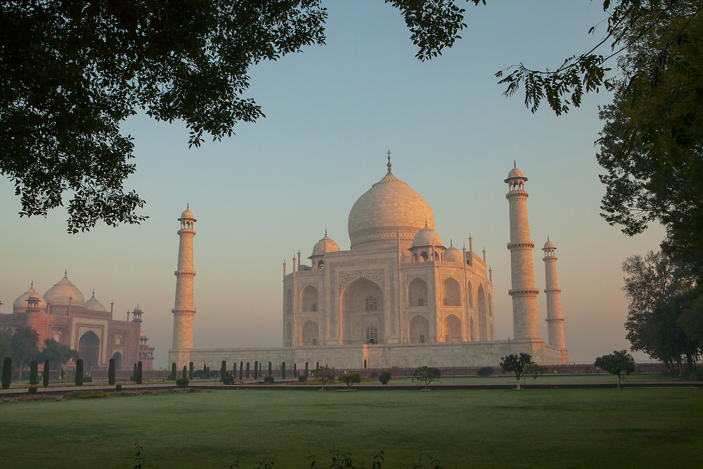 The Taj Mahal at sunrise. It is an ivory-white marble mausoleum on the southern bank of the river Yamuna in the Indian city of Agra