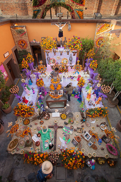 North America, Mexico, San Miguel de Allende, view from above of courtyard with elaborate altar with food, photographs and marigolds for Day of the Dead celebration, also known as Dios de los Muertos.  Mexicans celebrate the Day of the Dead on November 1st and 2nd in connection with the Catholic holy days of All Saints' Day and All Souls' Day.  PR