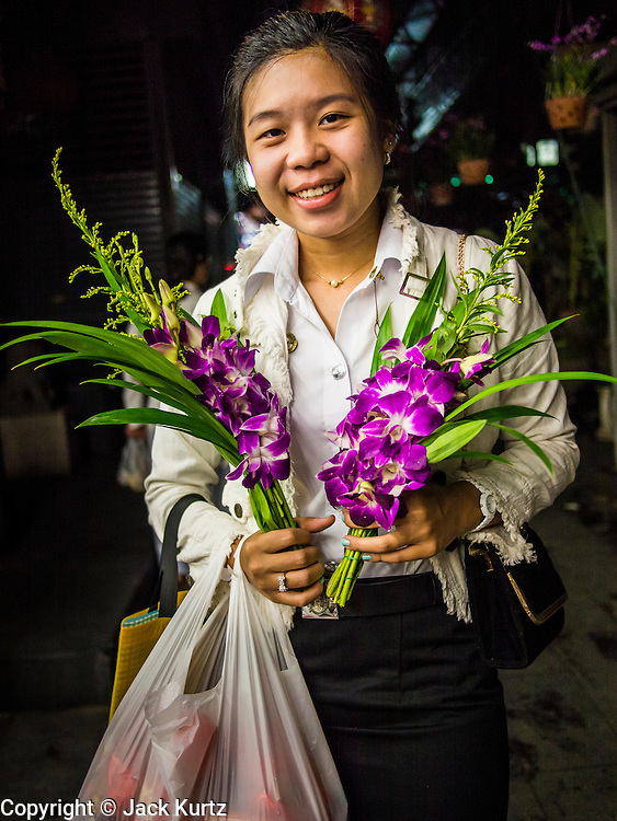08 SEPTEMBER 2013 - BANGKOK, THAILAND:  A woman carries flowers into the site of a mass alms giving service in Bangkok Sunday. 10,000 Buddhist monks participated in a mass alms giving ceremony on Rajadamri Road in front of Central World shopping mall in Bangkok. The alms giving was to benefit disaster victims in Thailand and assist Buddhist temples in the insurgency wracked southern provinces of Thailand.      PHOTO BY JACK KURTZ