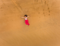 Aerial view of a happy woman lying on the beach of Cajueiro, Brazil.