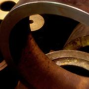 Closeup, warm-lit shot of various round pieces of steel shot in machine shop.