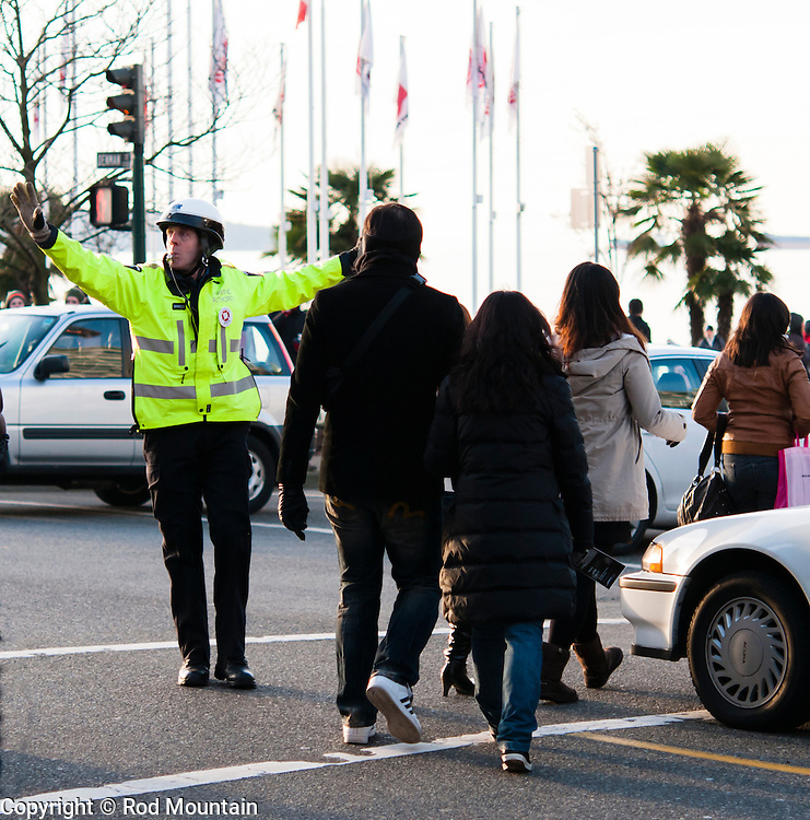 A Police Officer seen directing traffic near Denman Street in Vancouver. (Yellow jacket is accentuated using photo editing software)