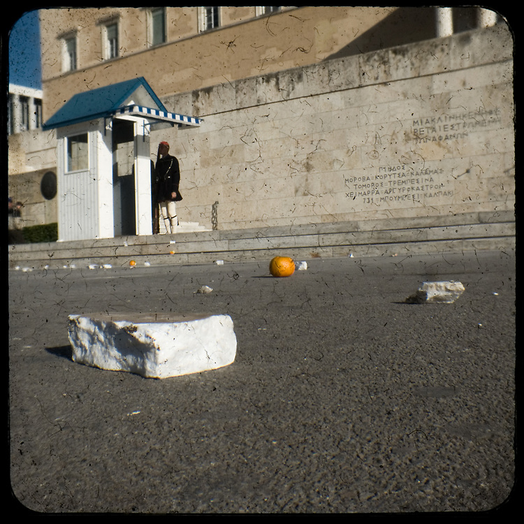 Bits of broken marble and bitter orange that have been previously thrown to the riot police lying in front of the presidetinal ceremonial guard in front of the Greek parliament. <br /> <br /> Following the murder of a 15 year old boy, Alexandros Grigoropoulos, by a policeman on 6 December 2008 widespread riots, protests and unrest followed lasting for several weeks and spreading beyond the capital and even overseas<br /> <br /> When I walked in the streets of my town the day after the riots I instantly forgot the image I had about Athens, that of a bustling, peaceful, energetic metropolis and in my mind came the old photographs from WWII, the civil war and the students uprising against the dictatorship. <br /> <br /> Thus I decided not to turn my digital camera straight to the destroyed buildings but to photograph through an old camera that worked as a filter, a barrier between me and the city.