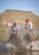 Pair of Gaucho's on horseback riding through water, Huechahue Ranch, Northern Patagonian Lake District, Argentina, South America