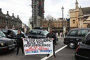 Licensed taxi drivers block the traffic in Parliament Square between 1pm-4pm in protest against traffic policies, 11th of February 2019, Central London, United Kingdom. A banner amongst the taxies. The disgruntled taxi drivers feel squeezed by local government transport policies. They say they will continue their protest and blockade the square every other day the same time until they feel the Mayor of London listens to them.