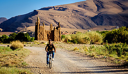 A young boy on a bicycle cycles passed a ruined Kasbah in the M'Guin Gorge in southern Morocco<br /> <br /> (c) Andrew Wilson   Edinburgh Elite media