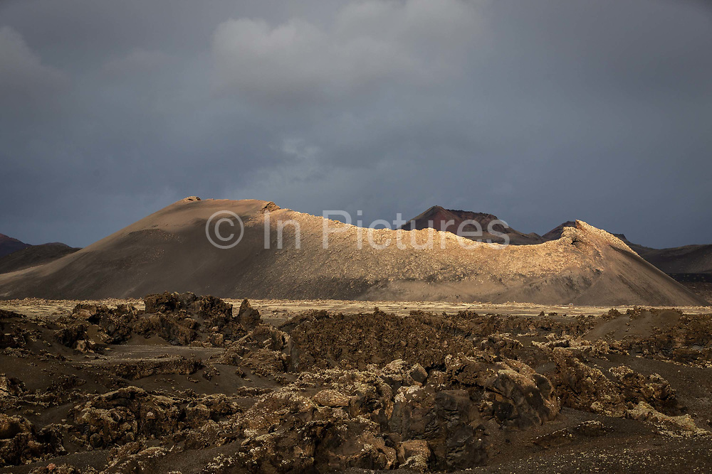 Waves of lava and volcanic peaks are illuminated by the morning sun on 26th November 2020, in Los Volcanes Natural Park in Lanzarote, Spain. The island was transformed by huge volcanic eruptions from 1731-36, which give it its unique dramatic landscape, and created the area now known as Timanfaya Natural Park, seen in the distance. .