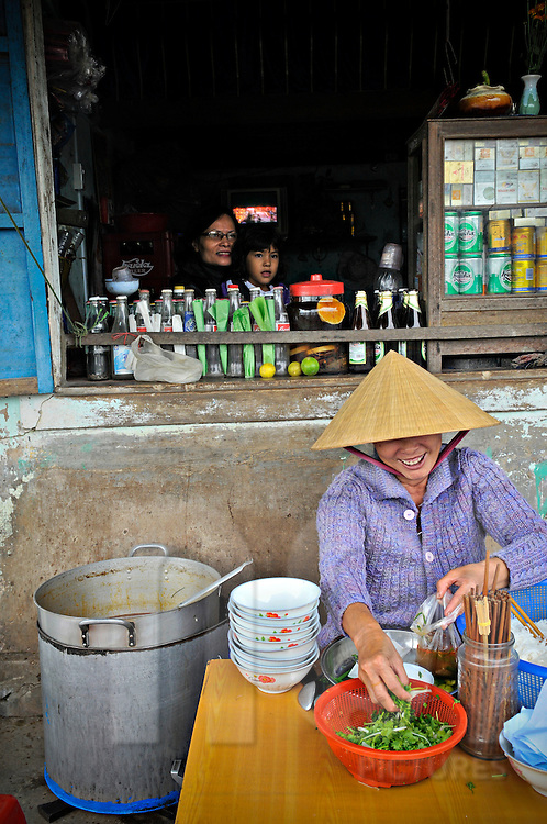 Daily life scene of a Vietnamese woman preparing noodle soup at a street food shop, Hue, Vietnam, Southeast Asia