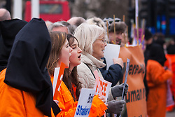 London, February 14th 2015. Dozens of orange boiler-suit clad protesters march from Parliament Square to Downing Street in protest against the ongoing detention in Guantanamo Bay of British subject Shaker Amer, who has been held without charge for 13 years.