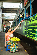A woman on a platform selling fruit and snacks to passengers on a train before departure, Central Railway Station, Yangon, Myanmar
