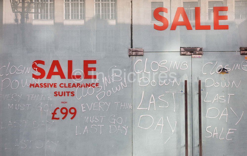 A closed business in Central London, a victim of the UK recession. The opaque windows of this business hide the failure of this shop in central London, not allowing us to understand why this retailer is ceasing trading during the UK recession. The large word Sale is written in red along the top with Closing Down and Last Day on both doors.