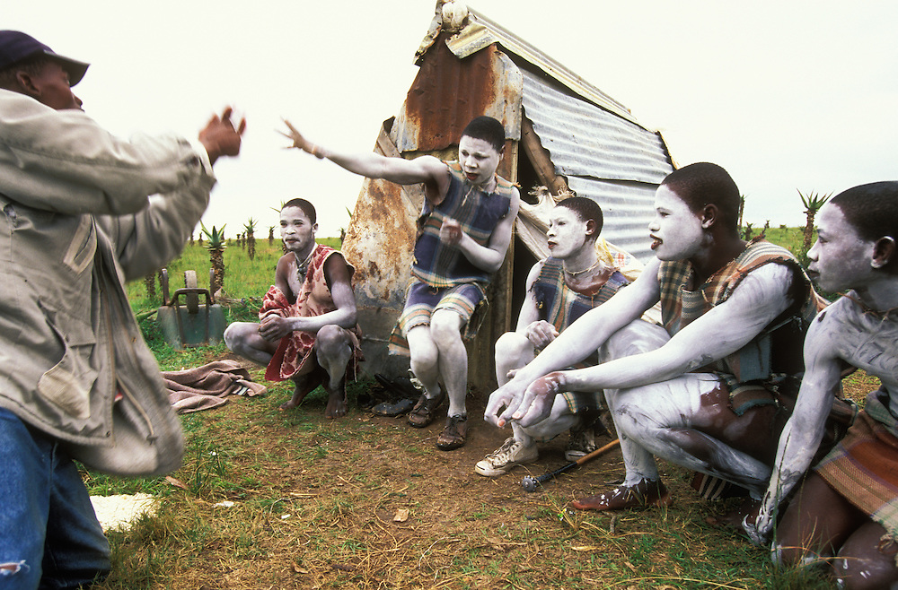Young Xhosa initiates, who spend about a month together in a special initiation camp, play traditional games with their guardian in Ciskei, Eastern Cape Province, South Africa, in December, 2006. The initiates go through the traditional Xhosa male initiation rite, which transforms them into adult men. They have been circumcised, and they wear white body paint to ward off attacks by witches.