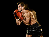 one caucasian young man boxer boxing profile side view  in studio isolated on black background