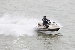 © Licensed to London News Pictures. 26/12/2014. The Solent, Hampshire, UK. Men on jet skis today, Boxing Day, playing on the wake of the Isle of Wight car ferry in The Solent. Photo credit : Rob Arnold/LNP