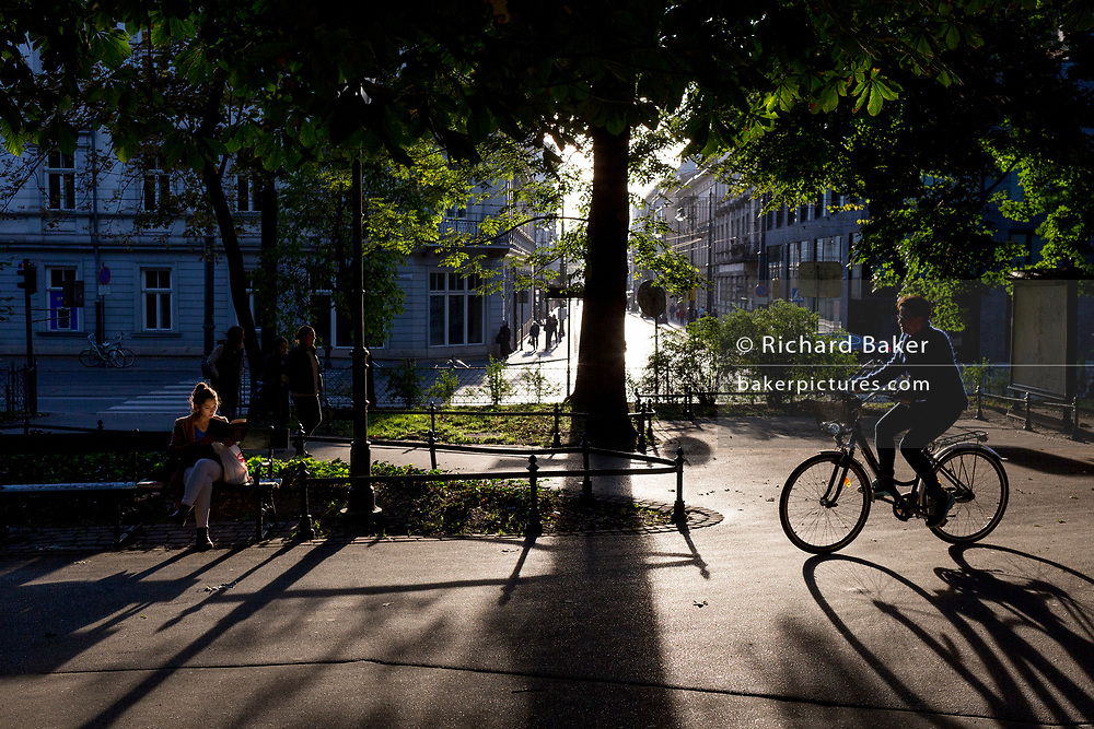Seated on a park bench, as a cyclist passes-by, a young Polish woman reads a book in late afternoon sunshine, on 23rd September 2019, in Krakow, Malopolska, Poland.
