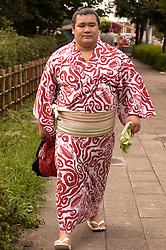 Sumo wrestler in yukata walking on Tokyo street to a competition