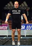 Adam Nelson removes T-Shirt solicting sponsorship as the 2005 IAAF World Outdooor champion prepares to throw in the shot put in the 99th Millrose Games at Madison Square Garden in New York City, N.Y. on Friday, February 3, 2006. Nelson finished third at 63-8 3/4 (19.42m).