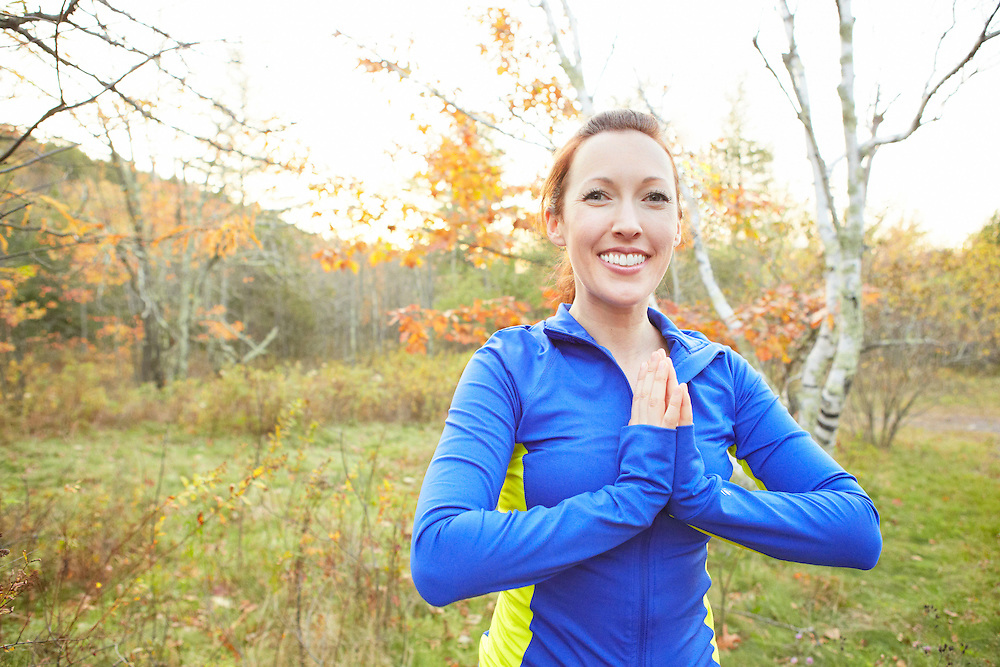 Lifestyle image of girl practicing yoga outdoors in autumn