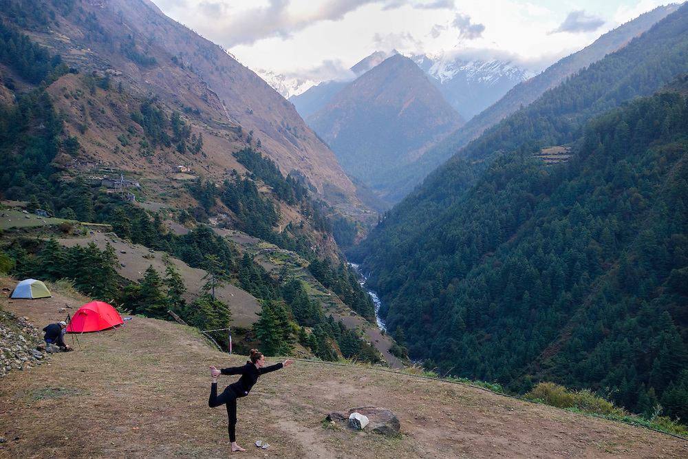 Trekkier doing yoga at a campsite in the Tsum Valley, Nepal.