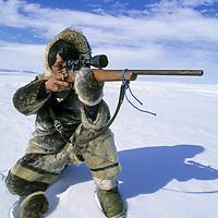 BAFFIN ISLAND, Nunavut, Canada. Inuit hunter Jayko Apak (MR) aims at a seal on frozen Sam Ford Fjord, Baffin Bay.