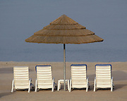 Beach chairs and umbrellas set up along the beach front of the Persian Gulf at the Hilton resort in Kuwait.