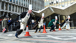© Licensed to London News Pictures. 05/03/2019. LONDON, UK.  Participants take part in the Inter-Livery Pancake Race, organised by the Worshipful Company of Poulters, at the Guildhall yard on Shrove Tuesday raising funds for the Lord Mayor's Charity.  All competitors have some association with the making of pancakes, for example the livery of Poulters supply the eggs, essential in the making of the pancakes.  Photo credit: Stephen Chung/LNP