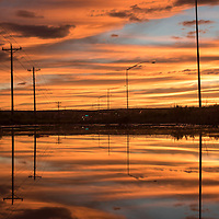 Sunset is reflected in the water in a ditch along Arizona road 264 in Window Rock Tuesday.