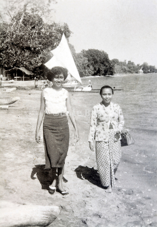 two woman walking by the water edge Indonesia, Java 1950s