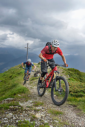 Mountain bikers riding on uphill in alpine landscape, Trentino-Alto Adige, Italy