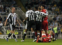Photo. Glyn Thomas. <br /> Newcastle United v Hapoel Bnei Sakhnin. <br /> UEFA Cup, 1st round, 1st leg. 16/09/2004.<br /> Abas Swan (R) lies on the ground after Newcastle's Nicky Butt (L) aimed a punch at him<br /> NORWAY ONLY