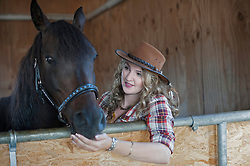 Young woman stroking her brown horse in barn, Bavaria, Germany