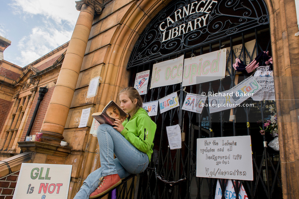 A teenage girl reads her book during the protest outside Carnegie Library in Herne Hill, south London while occupiers remain inside the premises on day 6 of its occupation, 5th April 2016. The angry local community in the south London borough have occupied their important resource for learning and social hub for the weekend. After a long campaign by locals, Lambeth have gone ahead and closed the library's doors for the last time because they say, cuts to their budget mean millions must be saved.
