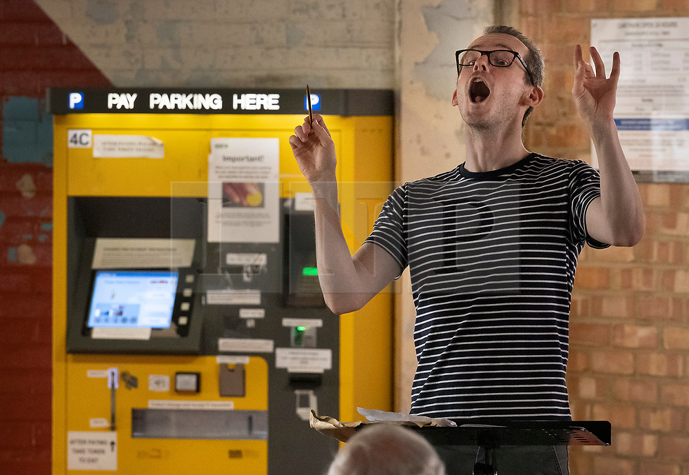 © Licensed to London News Pictures. 23/06/2021. Epsom, UK. Musical Director Julian Collings rehearses Epsom Choral Society in a multi-storey car park in Epsom, Surrey. The choir, in it's 99th year, has resorted to rehearsing in a socially distanced way on the 4th floor of the Ashley Shopping Centre car park after government Covid-19 regulations were updated to say that amateur choirs are only allowed to gather in groups of six indoors. Epsom and Ewell Borough Council agreed to the use of the car park which allows the choral society to rehearse in two groups of 30 outdoors but sheltered from the elements. Photo credit: Peter Macdiarmid/LNP