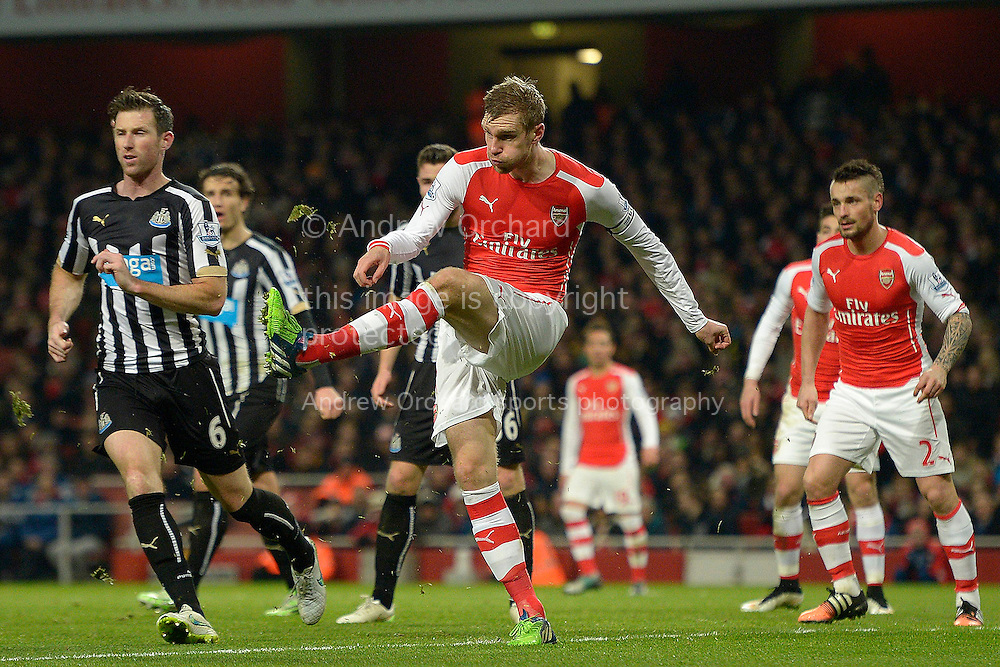 Per Mertesacker, the Arsenal Capt in action. Barclays Premier league match, Arsenal v Newcastle Utd at the Emirates Stadium in London on Saturday 13th December 2014.<br /> pic by John Patrick Fletcher, Andrew Orchard sports photography.