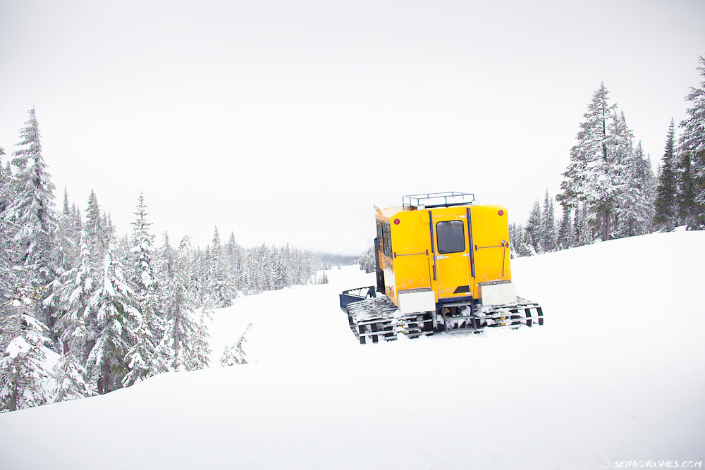 A snowcat grooming machine plows down a ski slope on top of a mountain.
