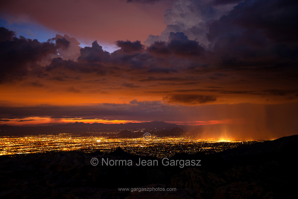 The city lights of Tucson glow at dusk during a full moon in September during a late monsoon squall at Windy Point in the Santa Catalina Mountains, Mount Lemmon, Sonoran Desert, Coronado National Forest, Arizona, USA.