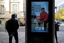 © Licensed to London News Pictures. 20/10/2020. Manchester, UK. A man walks past a sign on Market Street in Manchester reminding people to make space. Manchester is expecting to be forced in to a Tier 3 lockdown unless a deal is agreed. Photo credit: Kerry Elsworth/LNP