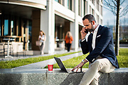 Businessman working on a laptop and talking on the phone, sat on a wall outside the International FInance Centre building in St Helier, Jersey, CI